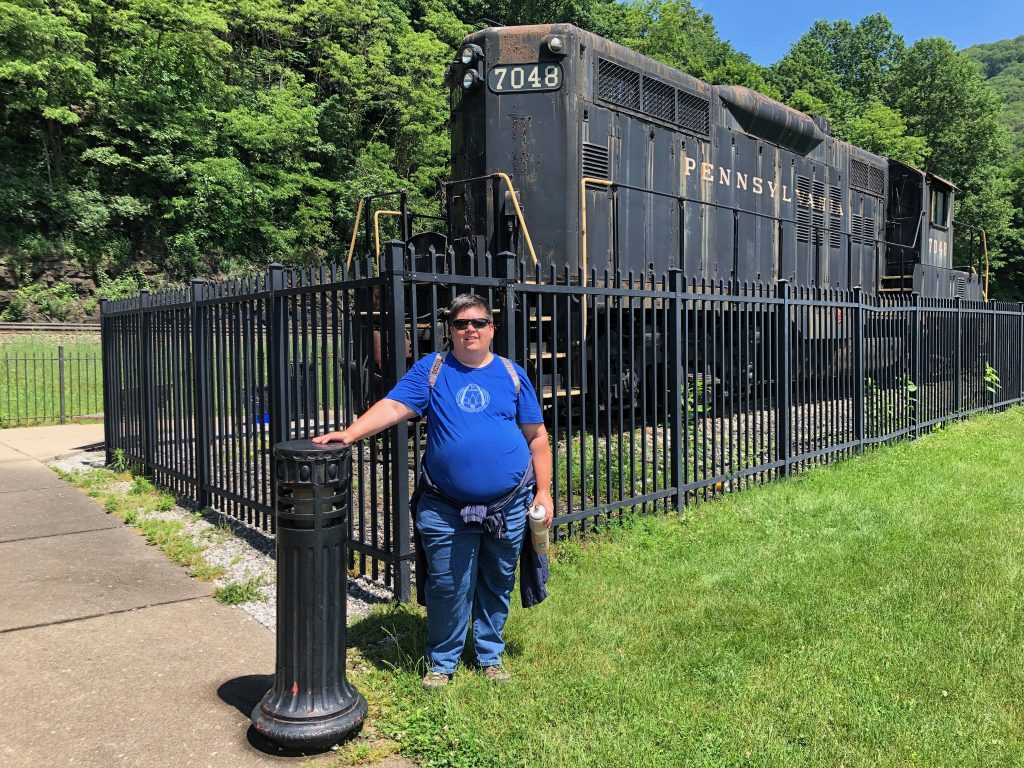 A woman standing in front of a vintage diesel locomotive