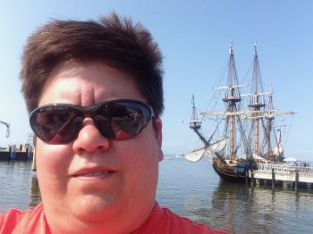 A woman standing in front of a vintage sailing ship